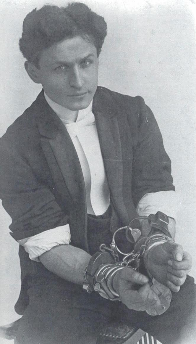 image of Harry Houdini with his wrists wrapped in 4 sets of handcuffs