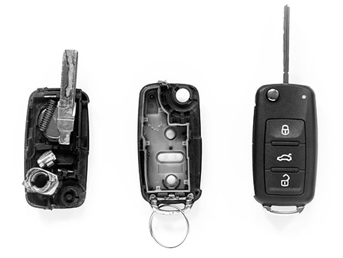 image of two badly damaged car key fobs on the left and a repaired one on the right